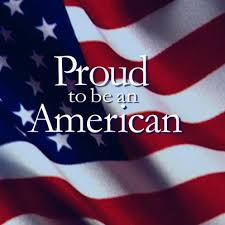 """US flag, ruffled by the wind, with the iconic motto """"Proud to be an American'"""