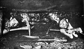 Two miners, flat on their bellies only enough rough for their helmets to touch the ceiling Google Images