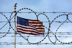 US Flag behind barbed wire Google Images