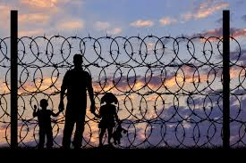 Silhouette of people behind a barbed wire fence. Google Images